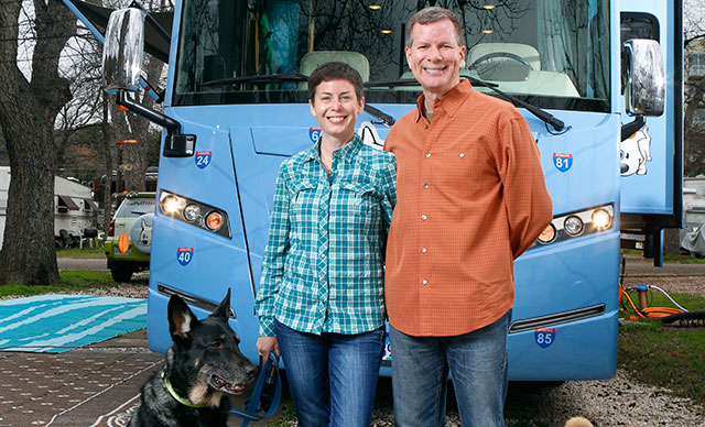 Rod Burkert, CPA/ABV, and his wife, Amy Burkert, CPA/ABV, stand in front of the RV that serves as their mobile office and their home.