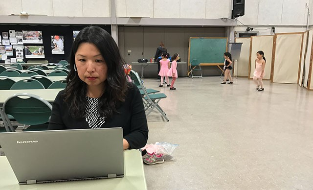 Alisa Nishimoto, director of client services, below, works while her daughter takes dance class.