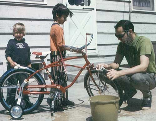 Scott Sprinkle (center) washes a bicycle with his younger brother, Sean, and his father, Stan.